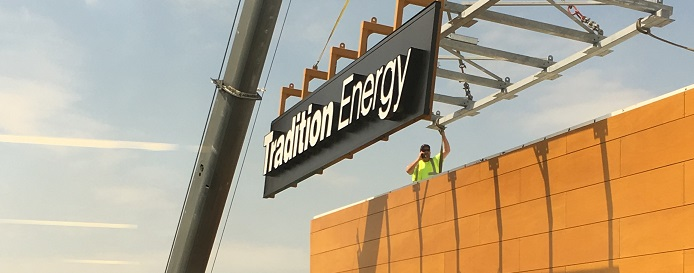 Tradition energy sign being installed by construction worker,