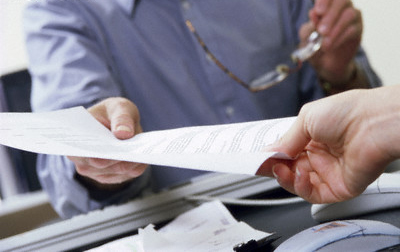 Handing Off Paperwork --- Image by © Cha Cha Royale/Brand X/Corbis